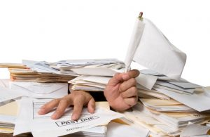 Man buried in paperwork and bills. All you see of him are his hands waving a surrender flag. White background with clipping path.